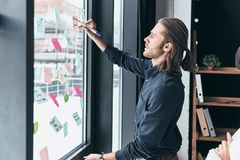 Working through some concepts. Modern young man in smart casual. Wear using adhesive notes on the window while working with his colleague in the office royalty free stock image