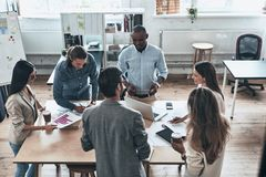 Working through some concepts. Top view of young modern people i. N smart casual wear discussing business while standing in the board room royalty free stock photo