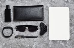Working space. Accessories for a business woman on a concrete table. Space for text. Wallet, sheet of paper, perfume, sunglasses royalty free stock image