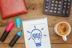 Working space. Drawing lamp in notebook with text: idea Stock Photography