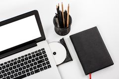 Working space with laptop, disc, notebook and stationary. Portrait of working space with laptop, disc, notebook and stationary on white bakcground royalty free stock images