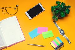 Working space with a notebook, pen, clock, telephone, headphones on a yellow background. place for text. The working space of a fr royalty free stock photos