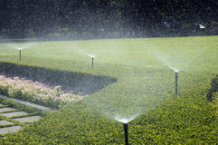 Working Sprinklers in grassland Royalty Free Stock Photos