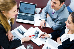 Working strategy. Image of business woman explaining and pointing to her project to colleagues Stock Images