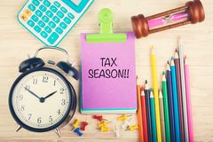 Calculator, clock, hourglass and Tax Season word written on notepad. Working table with calculator, clock, hourglass and Tax Season word written on notepad stock image