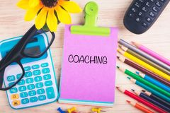 Calculator, pencils, thumbtacks and COACHING word written on notepad. Working table with calculator, pencils, thumbtacks and COACHING word written on notepad stock images