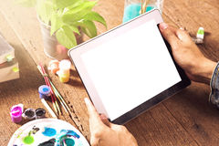 Working with tablet. The artist working with tablet on wooden desktop Stock Image