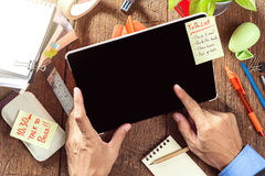 Working with tablet. Businessman working with tablet on wooden desktop Royalty Free Stock Image