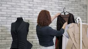 Woman fashion designer in workshop chooses clothes hang on hangers in atelier. Working in tailoring business factory. Unrecognizable woman fashion designer in stock footage