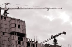 Working tall cranes inside place for with tall buildings under construction against a clear blue sky. Crane and building working. Progress. Retro tone royalty free stock photography