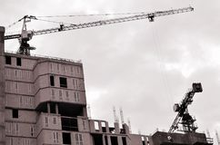 Working tall cranes inside place for with tall buildings under construction against a clear blue sky. Crane and building working. Progress. Retro tone royalty free stock photos
