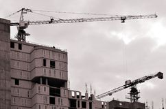 Working tall cranes inside place for with tall buildings under construction against a clear blue sky. Crane and building working. Progress. Retro tone royalty free stock image