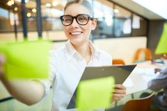 Working tasks. Young manager or secretary reading working reminders on noticeboard in office Stock Images