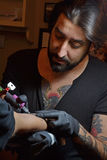 Working tattooing an arm. Royalty Free Stock Photo