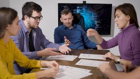 Working team are communicating in meeting in office, quarreling and one man is throwing papers and going away stock footage