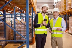 Nice serious men working together. Working team. Nice serious men standing in the warehouse while working together in team royalty free stock photography