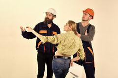 Working team. Technical task concept. Woman customer asks for repair, renovation. Brigade of workers, builders in. Helmets, repairers and lady customer royalty free stock image