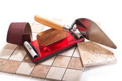 Before working tiler. Tiles, trowel, spatula, sandpaper on a white background Royalty Free Stock Images