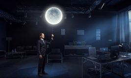 Working till late night. Mixed media. Businessman with moon balloon in dark office. Mixed media Stock Photos