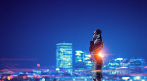 Working till late night . Mixed media. Young businesswoman with mobile phone against night city background Royalty Free Stock Photography