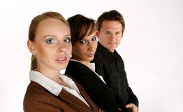 Working together. Three models looking at the camera. The main focus is on the woman in the foreground Royalty Free Stock Photo