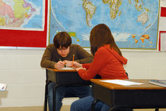 Working together. Two teens work together on a lesson in classroom Royalty Free Stock Photography