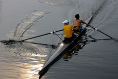 Working together. Two men in a racing scull Royalty Free Stock Images