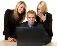 Working together. One business man sitting at desk in front of a computer with two woman coworkers standing behind him all looking at computer screen Royalty Free Stock Photos