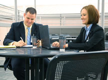 Working Together Outdoor. Two business people discussing business outdoor with laptop on outdoor sitting royalty free stock image