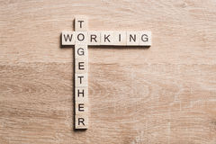 Working together words collected of game cubes on wooden surface Royalty Free Stock Photography