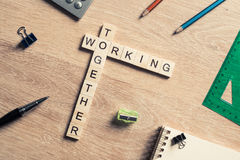 Working together words collected of game cubes on wooden surface Royalty Free Stock Image