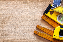 Working tools of measurement on oaken wooden board. Maintenance concept Stock Photos