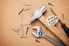 Working tools and note for Happy Fathers Day, cork board background, top view Royalty Free Stock Photography