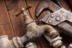 Working tools, plumbing, pipes and faucets. Plumbing tools lying with old pipes and faucets royalty free stock photography