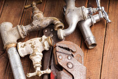 Working tools, plumbing, pipes and faucets. Plumbing tools lying with old pipes and faucets royalty free stock images