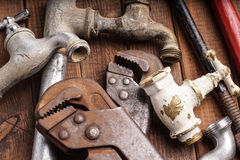 Working tools, plumbing, pipes and faucets. Plumbing tools lying with old pipes and faucets stock images