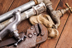 Working tools, plumbing, pipes and faucets. Plumbing tools lying with old pipes and faucets royalty free stock image