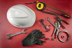Working tools on a red table. Several working tools, like a helmet, a hammer, a wrench, and other equipment, are spread on a red table. View from top Royalty Free Stock Images