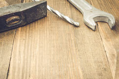 Working tools on a wooden surface. The hammer, drill and wrench on a wooden background Stock Image
