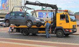Working tow truck in downtown Kaliningrad. KALININGRAD, RUSSIA — JULY 2, 2014: Working tow truck in downtown Kaliningrad Royalty Free Stock Image