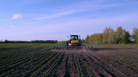 Working tractor and cultivator in the field. Shooting with crane stock video footage
