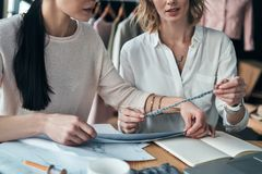 Working on trending designs. Close up young women working on swatches while sitting in the workshop stock photography