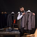 Working on trending designs. sewing mechanization. suit store and fashion showroom. Bearded man tailor sewing jacket stock images