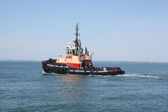 Working Tugboat,In The Ocean. This tugboat is heading to work Tugboats are powerful for their size and strongly built, and some are ocean-going. This one is just royalty free stock photos