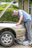 senior male works under the hood of his car stock photo