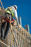 Working on the Wall. A construction worker on a high wall royalty free stock image
