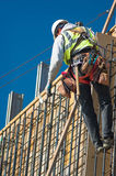 Working on the Wall. A construction worker on a high wall royalty free stock photography