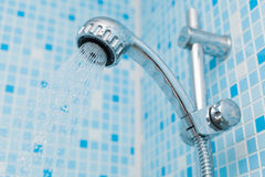 Working water head shower on blue background Royalty Free Stock Photos