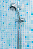 Working water head shower on blue background Royalty Free Stock Images