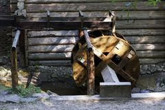 Working water mill wheel with falling water in the village. Sustainable energy and water power traditional machinery